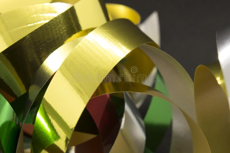 Metallic Ribbons. This is a photograph of Gold,Silver,Green and Red Metallic Ribbons placed infront of a Black background royalty free stock photography
