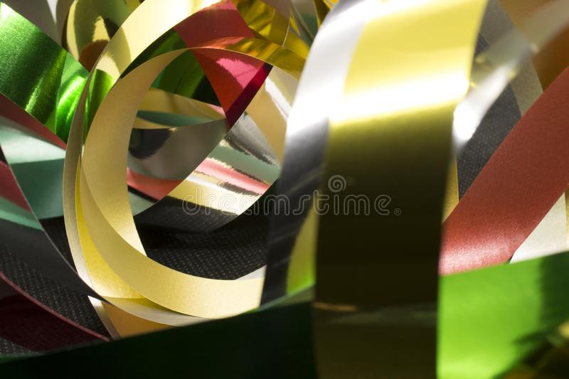 Metallic Ribbons. This is a photograph of Gold,Silver,Green and Red Metallic Ribbons placed infront of a Black background royalty free stock photo
