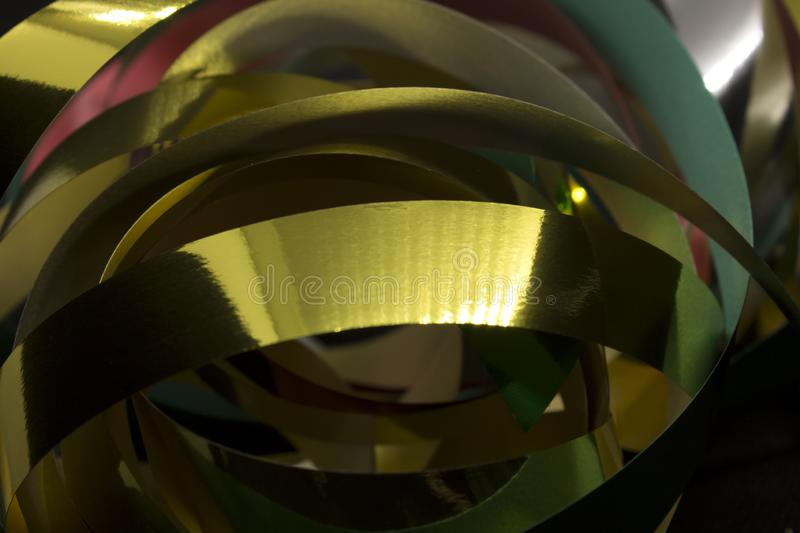 Metallic Ribbons. This is a photograph of Gold,Silver,Green and Red Metallic Ribbons placed infront of a Black background royalty free stock images