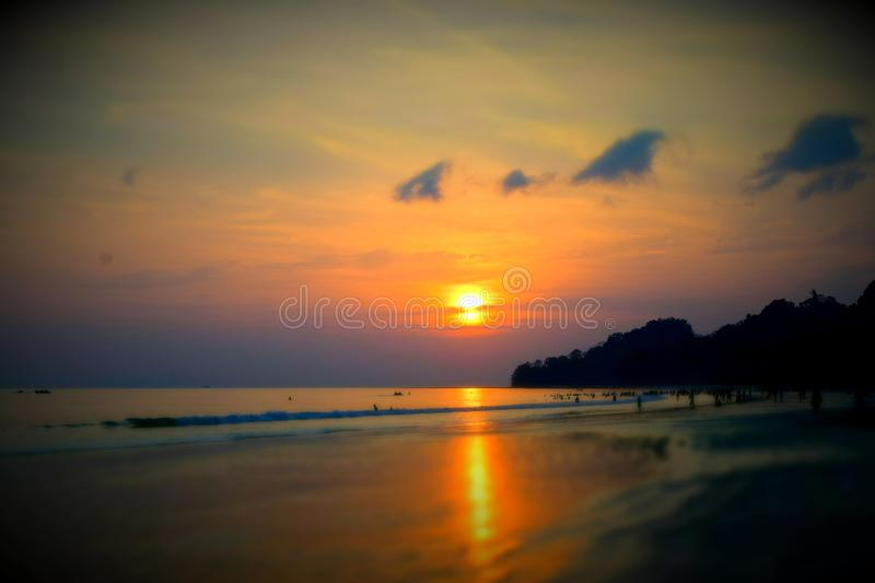 Golden Sun Setting over Ocean in Colorful Sky - Vignette - Natural Abstract Blur Background. This is a photograph of golden sun setting over ocean in colorful stock images