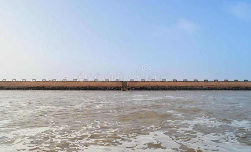 Gomti River at Ghat and row of Benches on Shore - Devbhumi Dwarka, Gujarat, India - Water and Environment. This is a photograph of Gomti River, which is stock photo