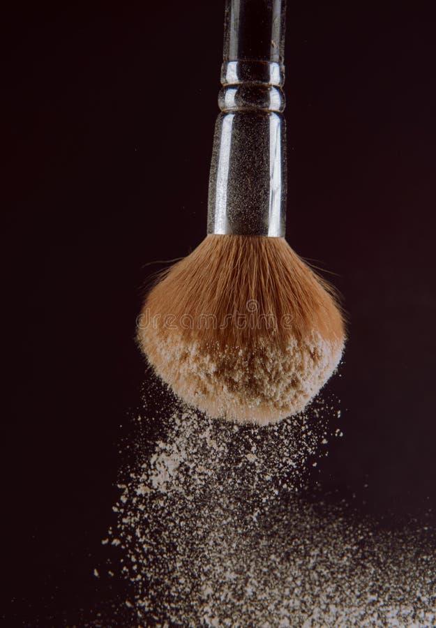 Isolated make-up powder with brush on black background stock photography