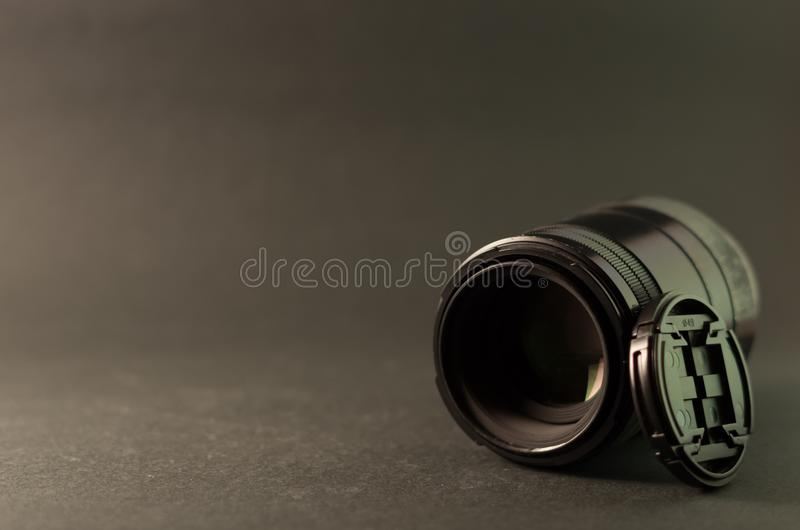 Macro lens and lens cap. Photograph of a macro lens and lens cap on grey background royalty free stock photos
