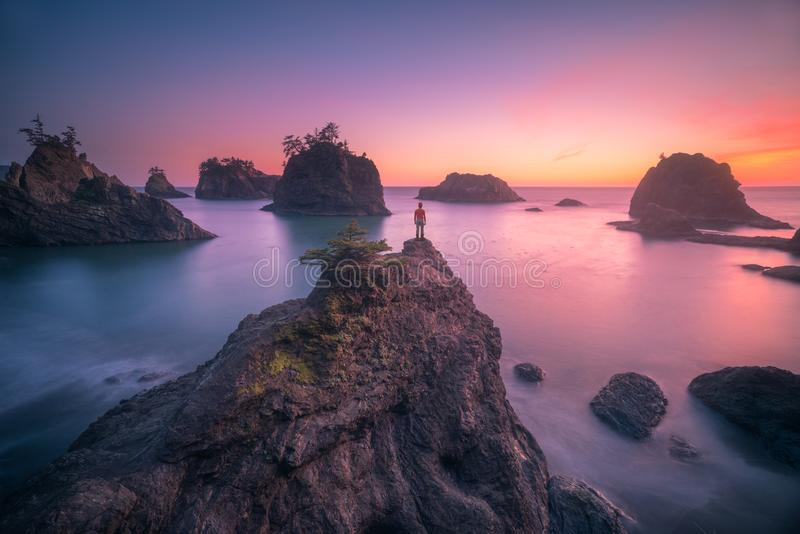 Watching sunset of Oregon coast. This is a photograph of a man standing on top of sea stack and watching sunset of Oregon coast royalty free stock photos