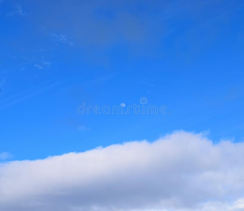 Moon in Clear Blue Sky with White Clouds - Natural Background stock images