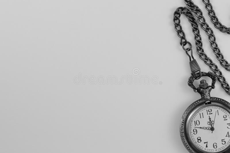 Antique gray metal pocket watch with chain isolated on light background. This photograph with an overhead perspective features an antique gray metal pocket watch royalty free stock images