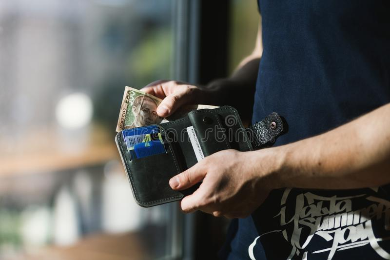 Photograph of Person Holding Black Leather Wallet with Money royalty free stock images