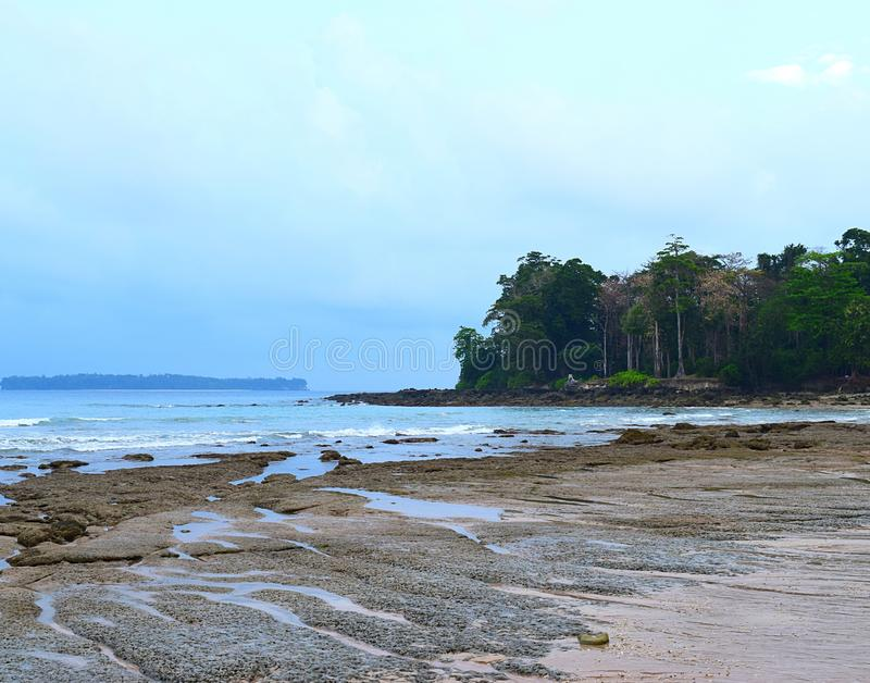 Quiet Sea Waves, Rocky Beach, Tall Trees and Clear Sky - Sitapur, Neil Island, Andaman Nicobar, India royalty free stock image