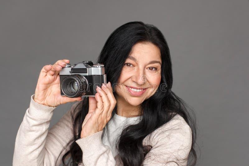 photograph Reife Damenstellung auf grauen nehmenden Bildern mit netter Nahaufnahme der Filmkamera stockbilder