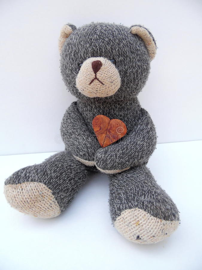 Photograph of Sad Teddy Bear Holding Heart. Photograph of a sad looking toy Teddy bear in full view. Teddy is holding a wooden heart. Photograph is oriented in royalty free stock images