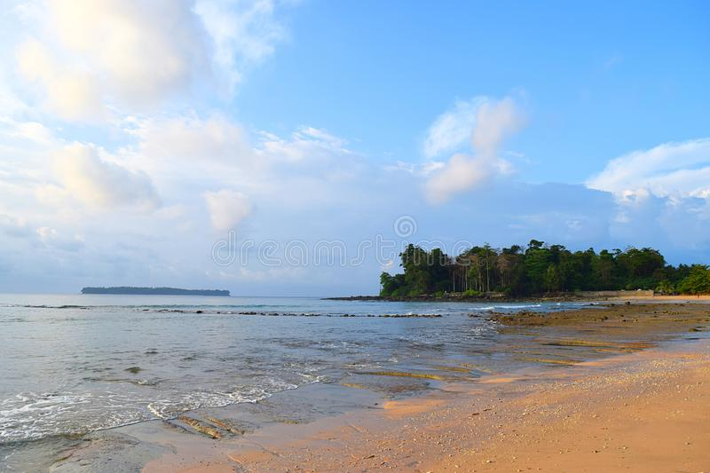 Sandy Beach, Calm Sea Waters, Greenery, Distant Island, & White Clouds in Blue Sky - Sitapur, Neil Island, Andaman Nicobar, India stock photography