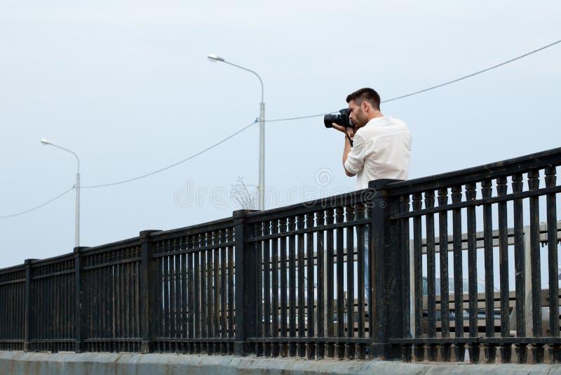 Photograph shoot from bridge. Man Photograph shoot from bridge in summer city stock image