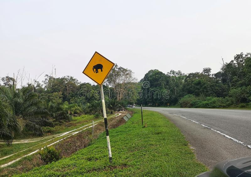 Traffic road sign alerting wild life, driving in Malaysia. A photograph showing the signage by the high way road passing through some forest nature area in the stock photography