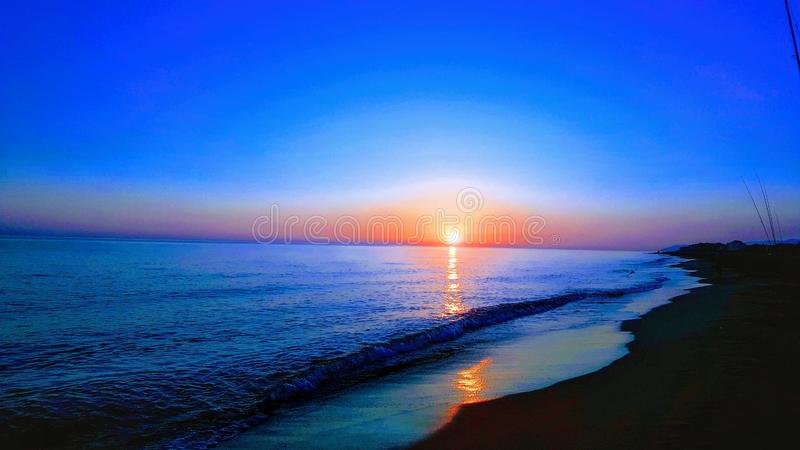 This photograph shows a sunset on the serene water beach at the optimum color point stock photography