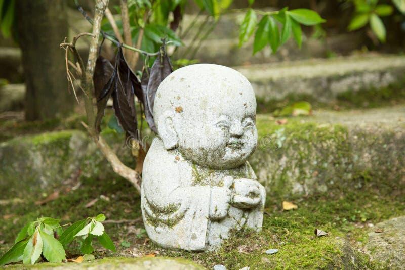 Photograph of a small buddha statue praying stock photo