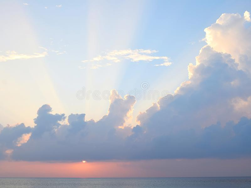 Sun Setting over Ocean with Rays through Clouds in Blue Sky royalty free stock photography