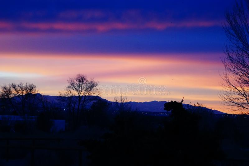 A sunset over the Sandia mountains in New Mexico. A photograph of a sunset over the Sandia mountains of New Mexico showing orange, yellow and blue colors royalty free stock photos