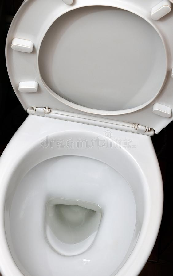 A photograph of a white ceramic toilet bowl in the dressing room or bathroom. Ceramic sanitary ware for correction of nee. D stock image