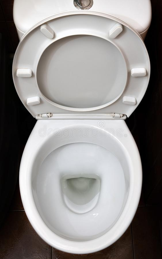 A photograph of a white ceramic toilet bowl in the dressing room or bathroom. Ceramic sanitary ware for correction of nee. D royalty free stock image