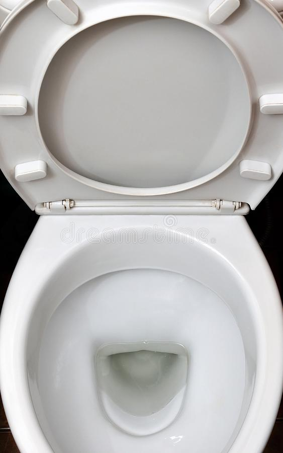 A photograph of a white ceramic toilet bowl in the dressing room or bathroom. Ceramic sanitary ware for correction of nee. D stock photos