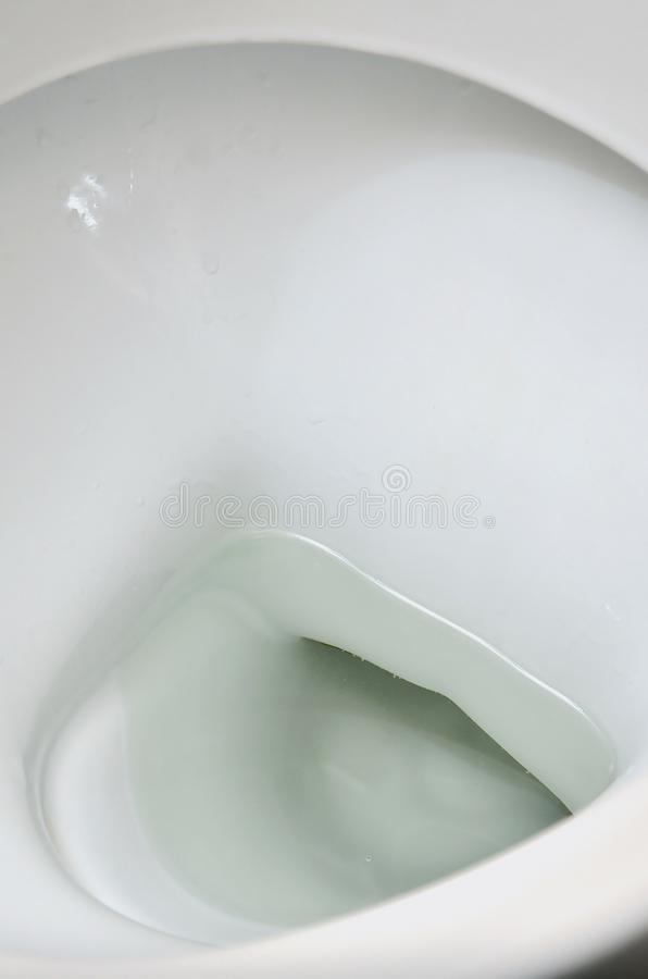 A photograph of a white ceramic toilet bowl in the dressing room or bathroom. Ceramic sanitary ware for correction of nee. D stock photo