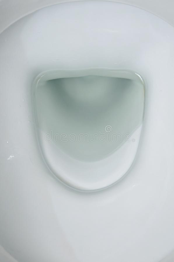 A photograph of a white ceramic toilet bowl in the dressing room or bathroom. Ceramic sanitary ware for correction of need. A photograph of a white ceramic royalty free stock image