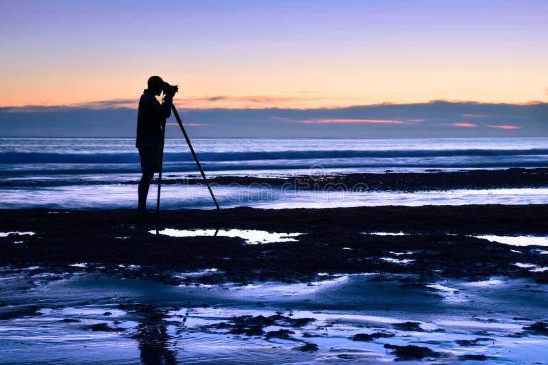 Photographe à la mer dans le crépuscule images libres de droits