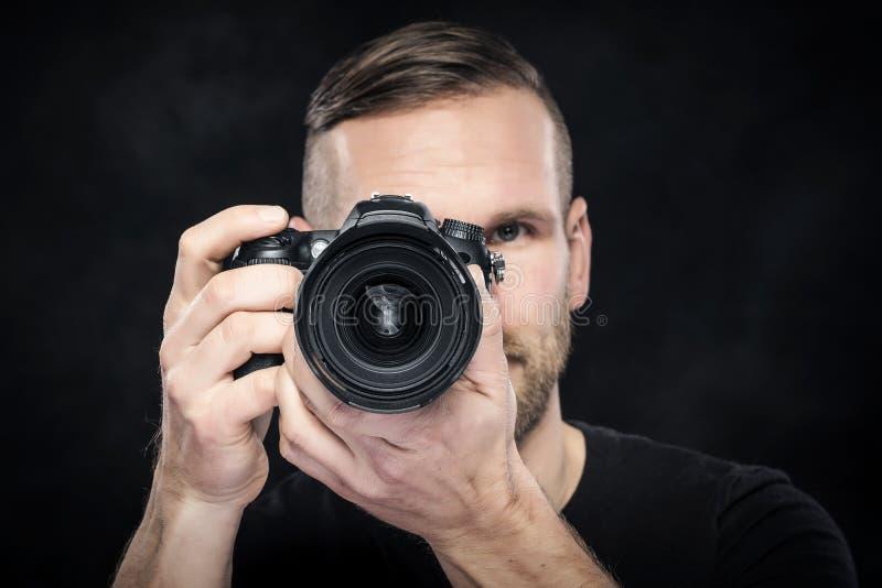Photographe avec l'appareil-photo sur le noir images stock
