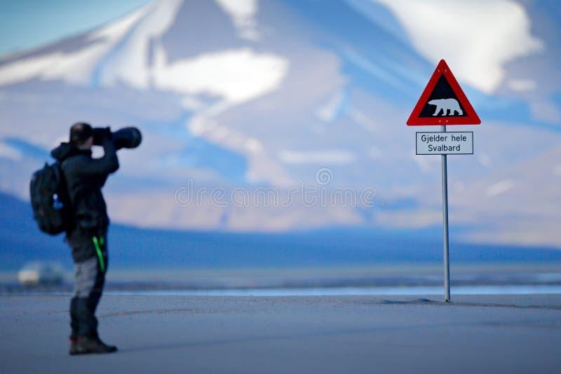 Photographe avec le grand signe de circulation routière de lentille et avec l'ours blanc les moyens de Gjelder Hele le Svalbard d photos stock