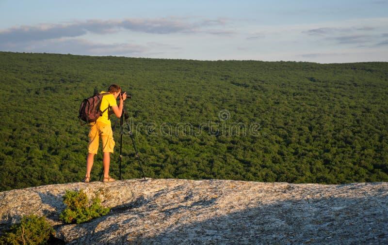 Photographe avec le trépied et le sac à dos sur la roche photo libre de droits
