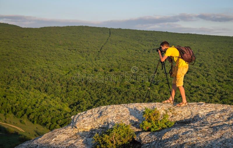 Photographe avec le tr?pied et le sac ? dos sur la roche photos libres de droits