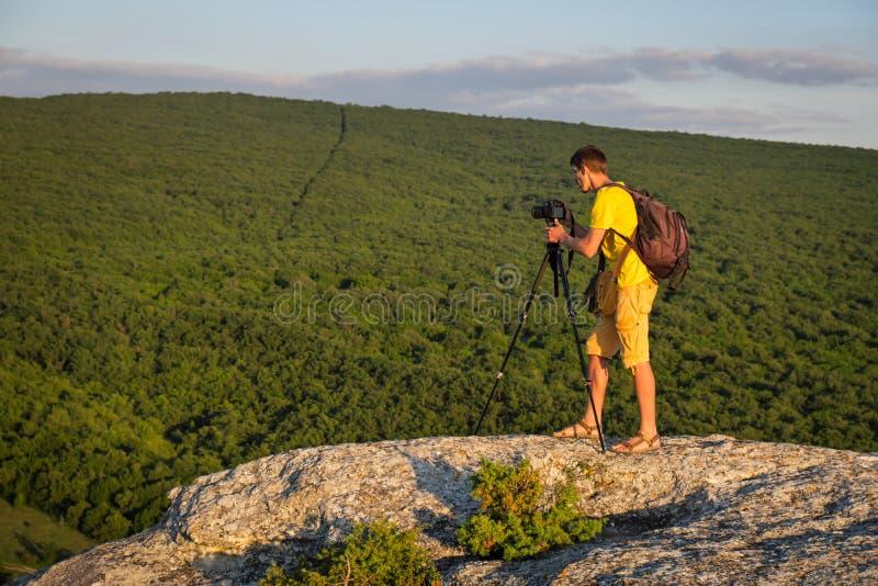 Photographe avec le tr?pied et le sac ? dos sur la roche photo stock
