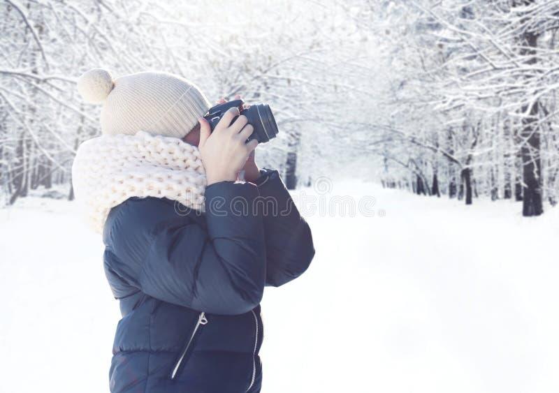 Photographe d'enfant avec la caméra prenant le paysage de forêt d'image en hiver neigeux photographie stock libre de droits
