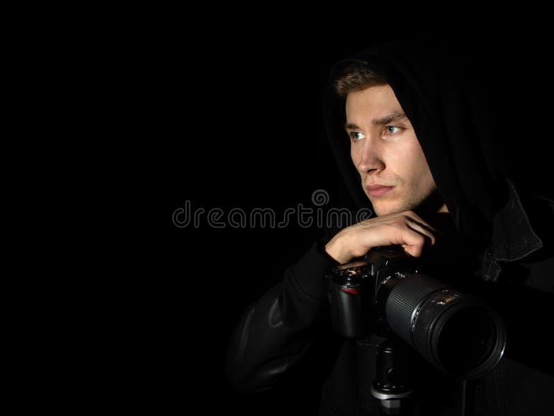 Photographe d'homme avec une caméra de DSLR sur un trépied à un arrière-plan noir d'isolement par capot noir photos libres de droits