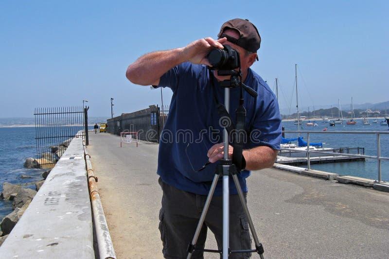 Photographe d'homme sur le pilier d'océan photographie stock libre de droits