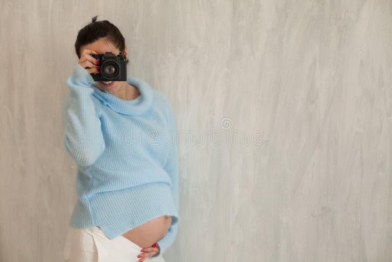 Photographe de femme enceinte avec une caméra 1 de film images stock