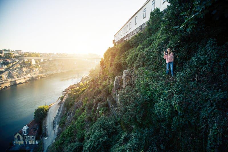 Photographe de fille se tenant sur une roche verte raide devant la rivière de Douro au centre ville de Porto photos libres de droits