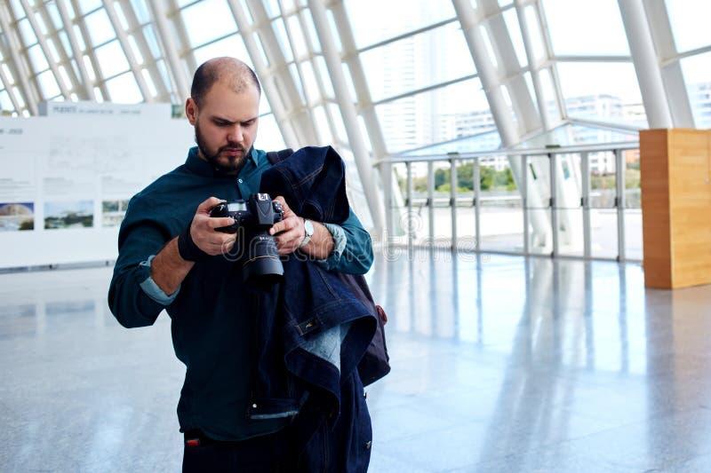 Photographe de jeune homme regardant les photos de la dernière séance photo photographie stock libre de droits