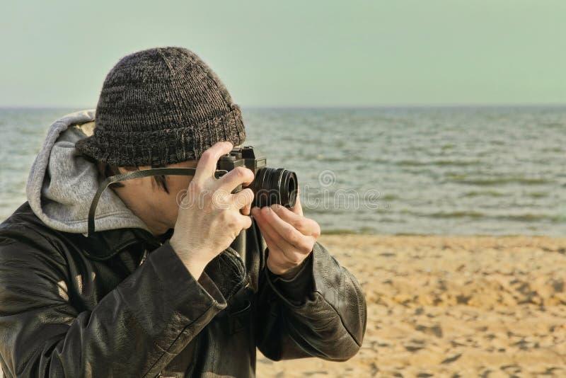 Photographe employant le rétro appareil-photo de photo sur la plage de mer photo libre de droits