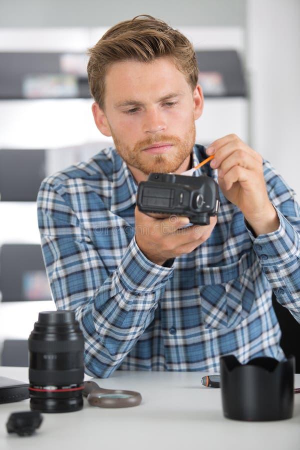 Photographe employant le stylo de brosse de nettoyage de lentille photo stock