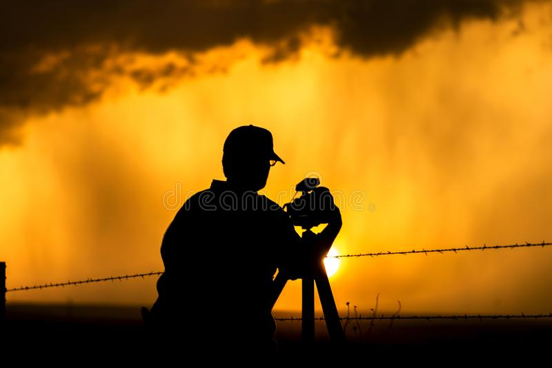 Photographe encadré contre le coucher du soleil photos stock
