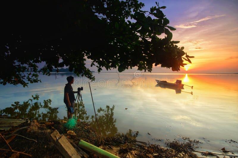 Photographe et bateau pendant le lever de soleil photo stock