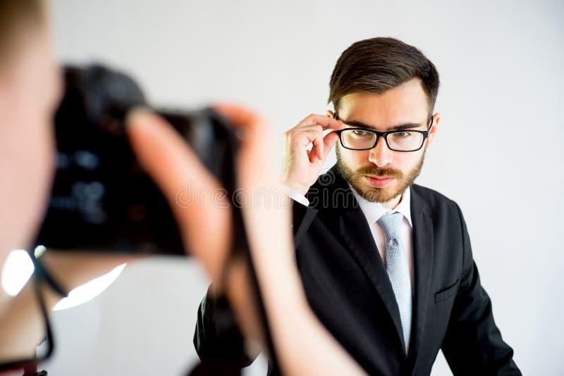 Photographe féminin prenant la photo d'un modèle masculin dans le studio images stock