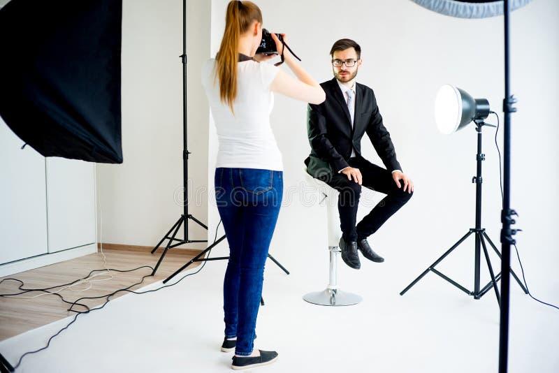 Photographe féminin prenant la photo d'un modèle masculin dans le studio photos stock