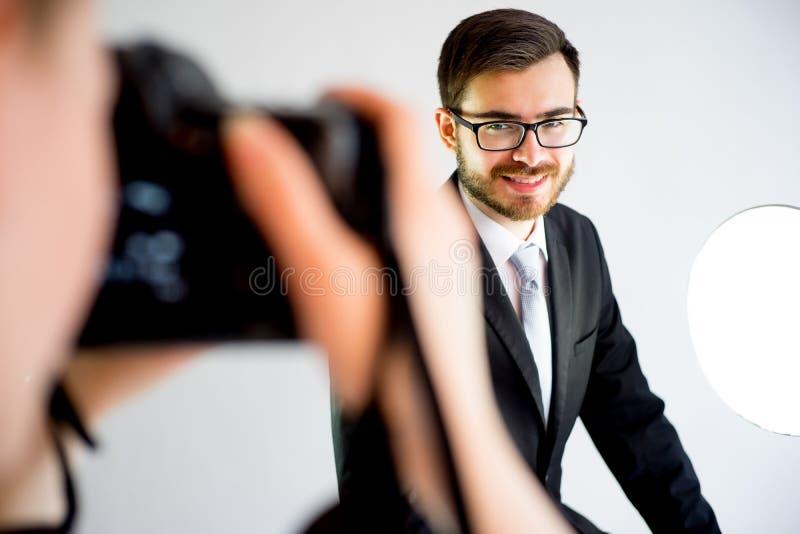 Photographe féminin prenant la photo d'un modèle masculin dans le studio photo stock