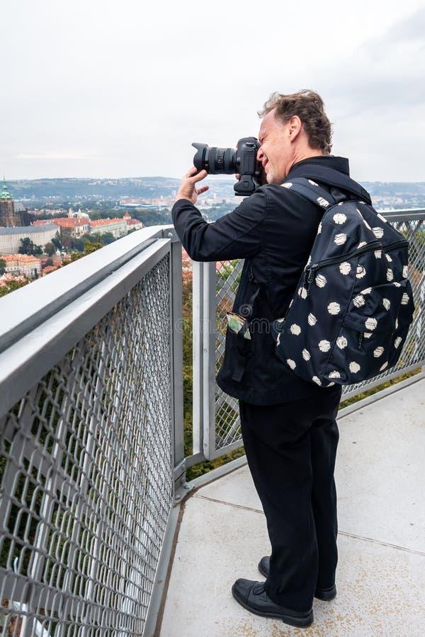 Photographe masculin caucasien dans le costume noir et sac à dos à une tour avec l'appareil photo numérique prenant des photos de images stock