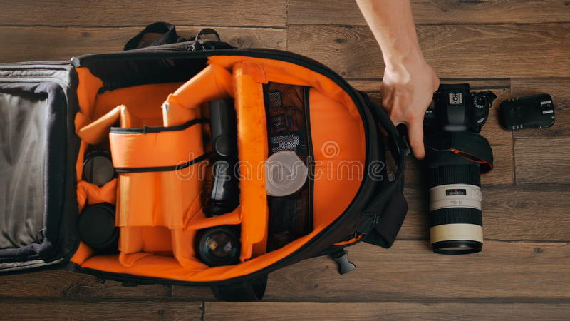 Photographe pack his camera and lenses to bagpack. Bag appliances for photography top view. stock images