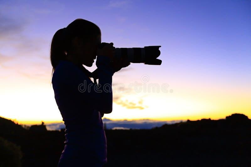 Photographe prenant des photos avec l'appareil-photo de SLR images stock