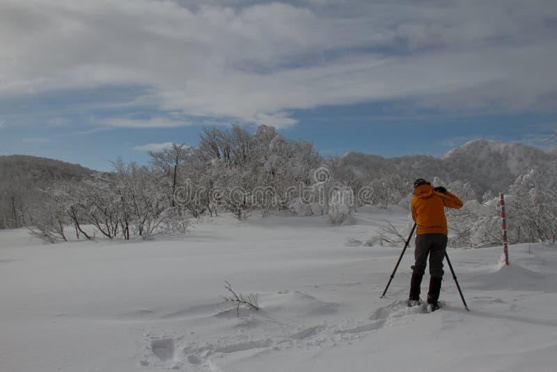 Photographe prenant des photos d'un paysage gentil d'une montagne congelée image stock