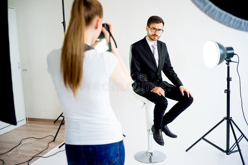 Photographe prenant la photo d'un modèle dans le studio images stock